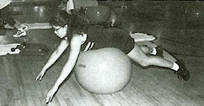 A member of Equinox's Surf Flex workout class balances on a large inflated ball.
